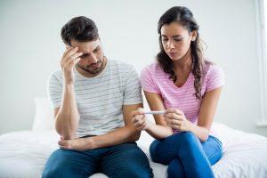 couple appearing frustrated looking at pregnancy test; blog: reasons you may be having trouble getting pregnant