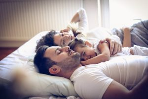 family with one child lying in bed; blog: secondary infertility