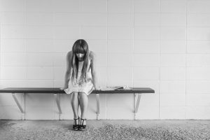 worried girl sitting on bench; blog: 4 Questions to Ask Before Talking with Others About Your Infertility