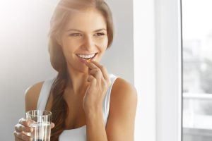 Diet. Nutrition. Vitamins. Healthy Eating, Lifestyle. Close Up Of Happy Smiling Woman Taking Pill With Cod Liver Oil Omega-3 And Holding A Glass Of Fresh Water In Morning. Vitamin D, E, A Fish Oil Capsules.; Blog: How to Prepare Your Body for Pregnancy
